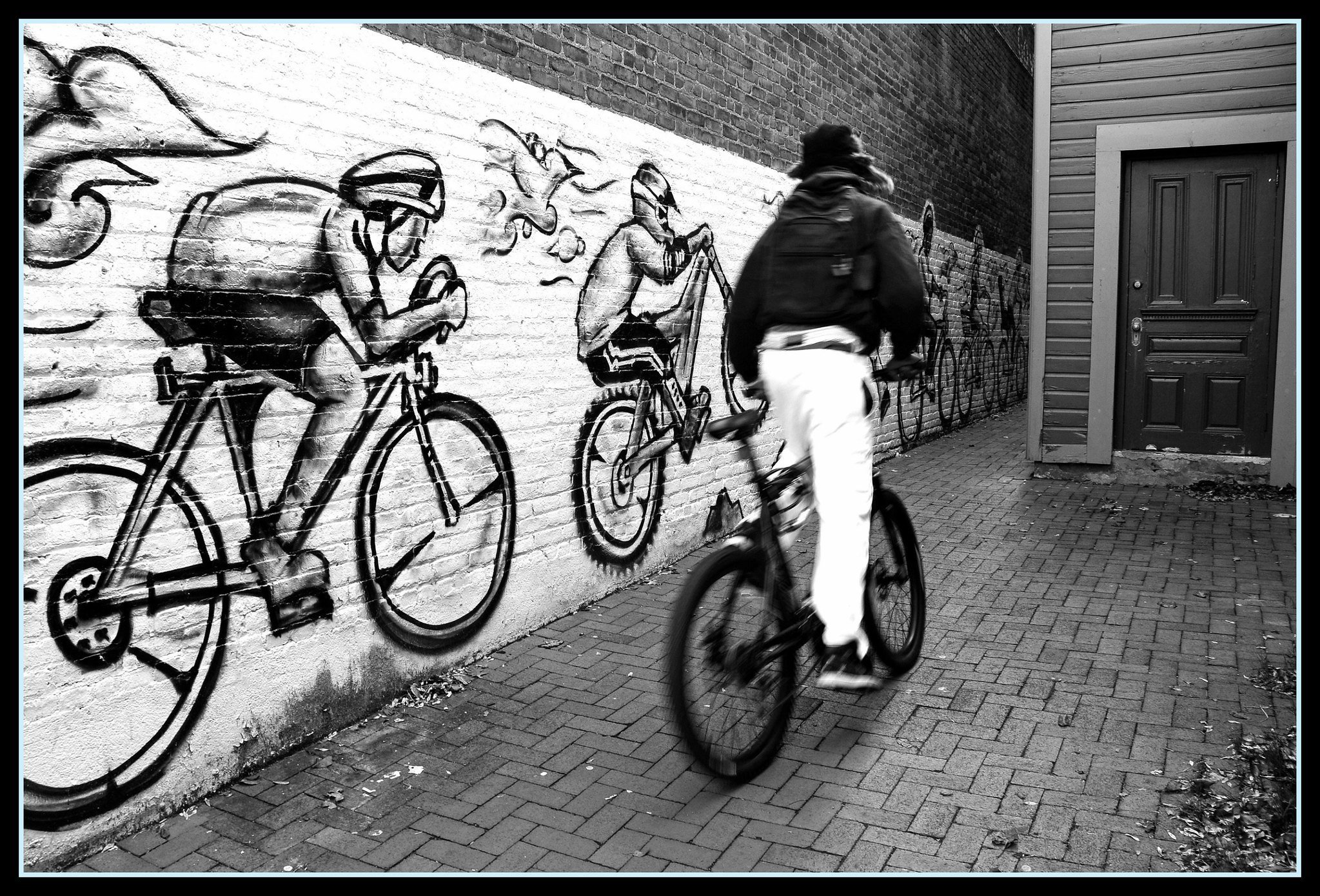 Someone biking down an alley with a mural of bikers in the background.