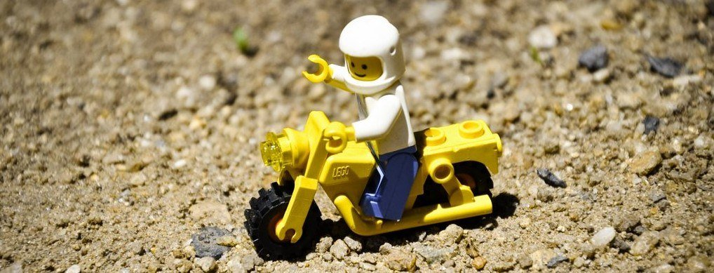 A picture of a LEGO on a yellow bike, and he's wearing a helmet!