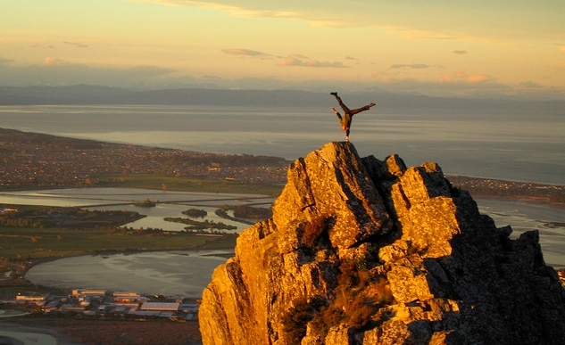 man does one-handed handstand on mountain
