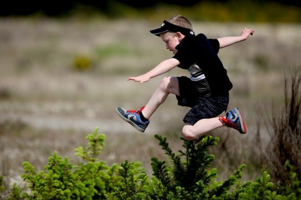 Boy Running Through a Field Jumping and Having Fun