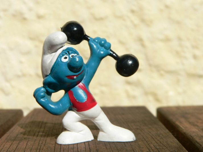 This Smurf lifts weights to grow strong.