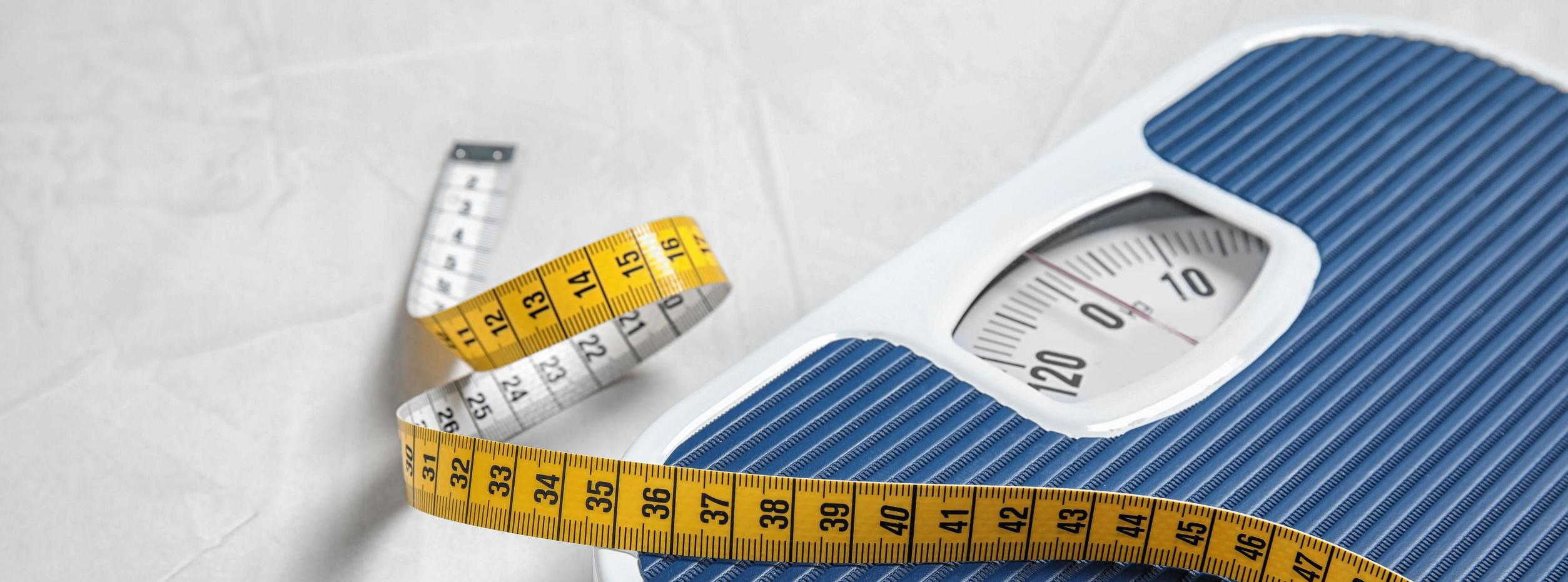 A picture of a scale and tape measure, tools for fast weight loss.