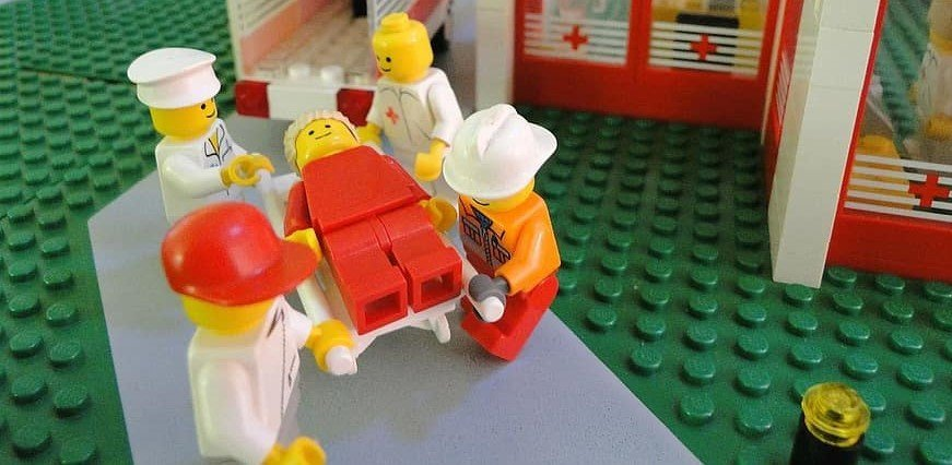 A picture of medics helping a LEGO, who is clearly very sore.