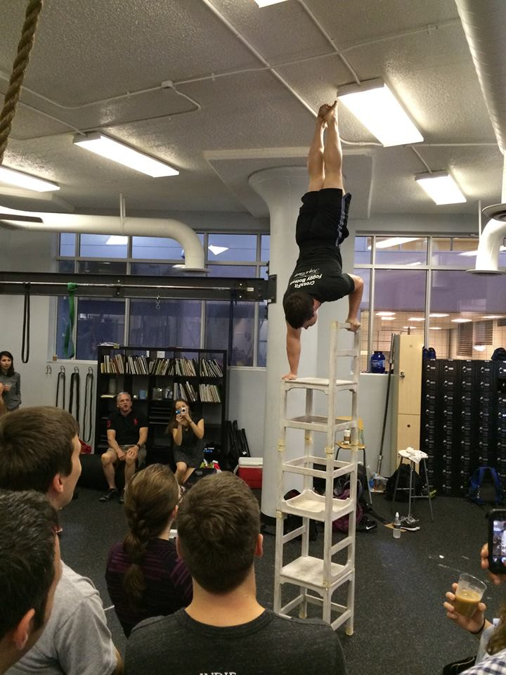 Coach Jim doing a handstand on stacked chairs.