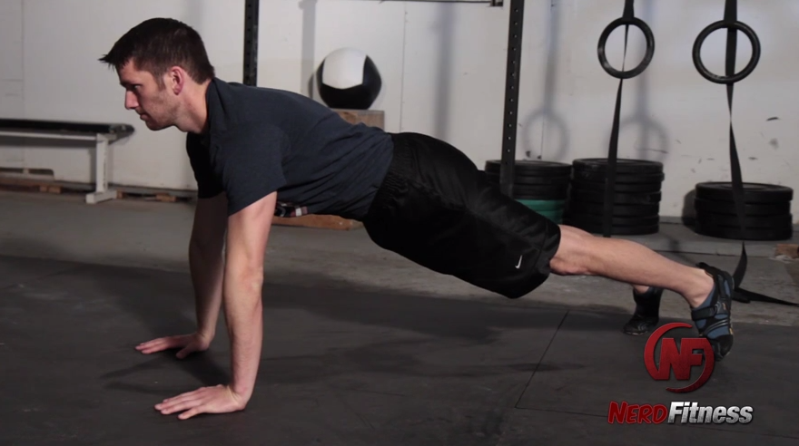 You'll start a wall walk by first getting comfortable in a plank position.