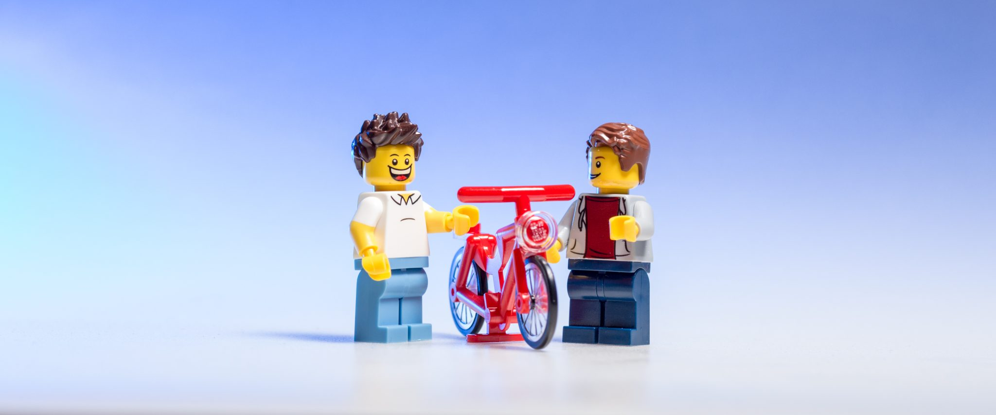 Two LEGOs discussing a bicycle.