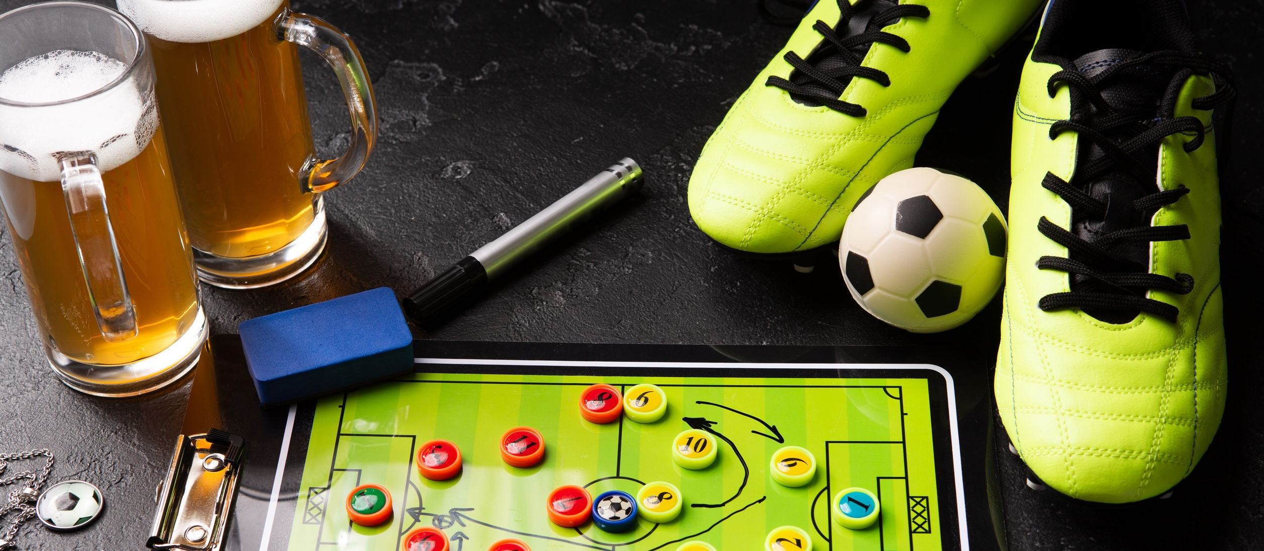 Photo of two mugs of foam beer, table football, ball, football boots, pipe, rattle toy on black table