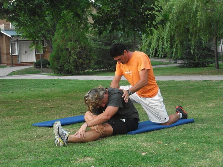 A personal trainer stretching out a client.