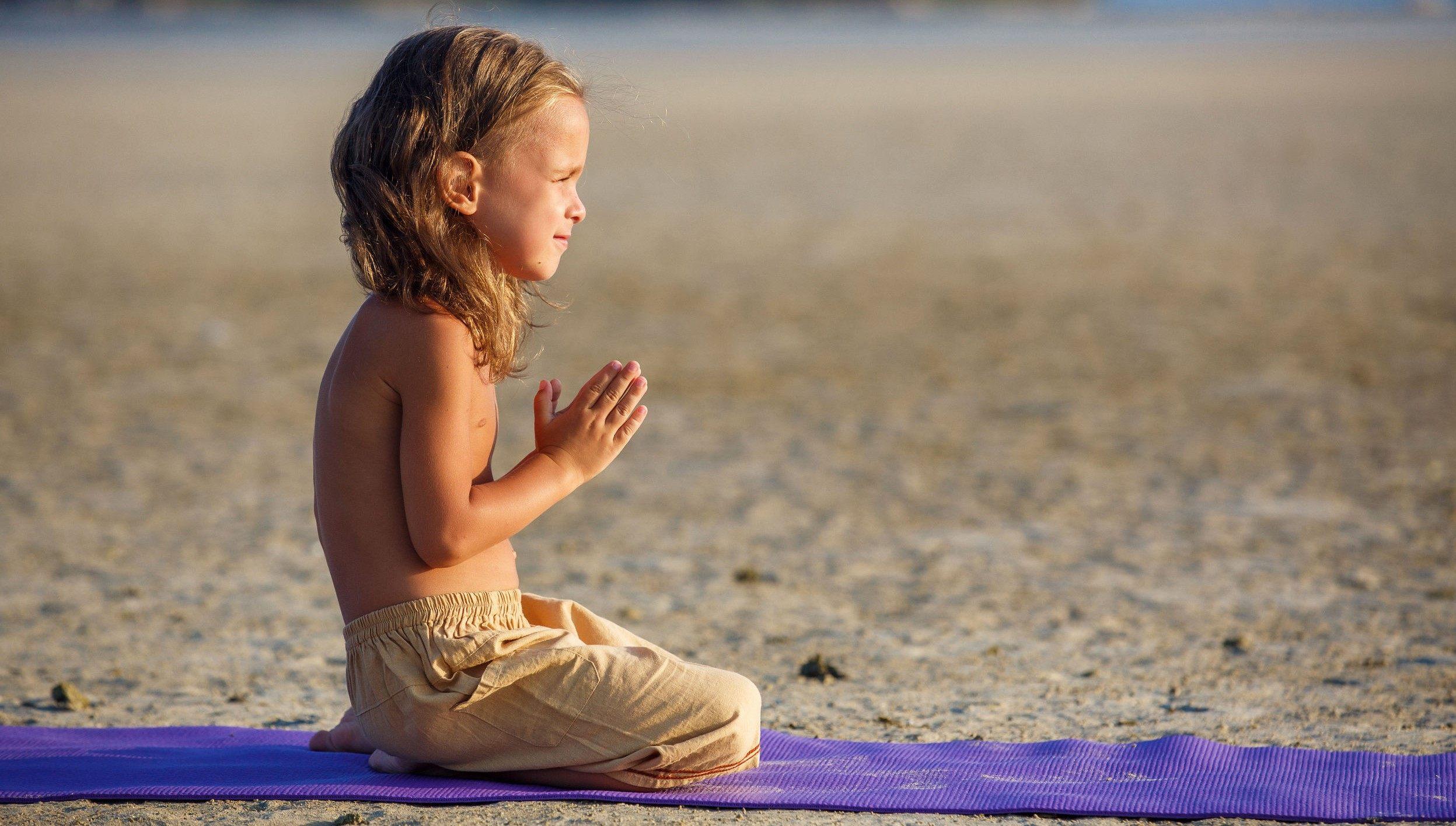 Boy on the beach doing yoga