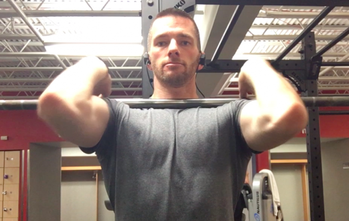 With your chest up and elbows up, grab the bar close to your shoulders