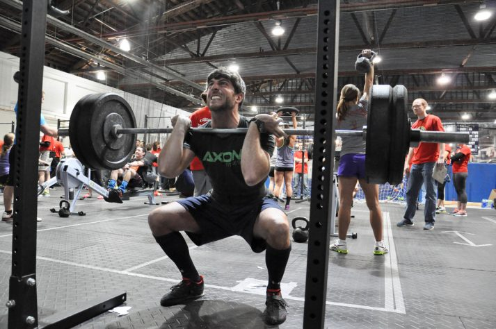 This pictures shows a man in the middle of a front squat.