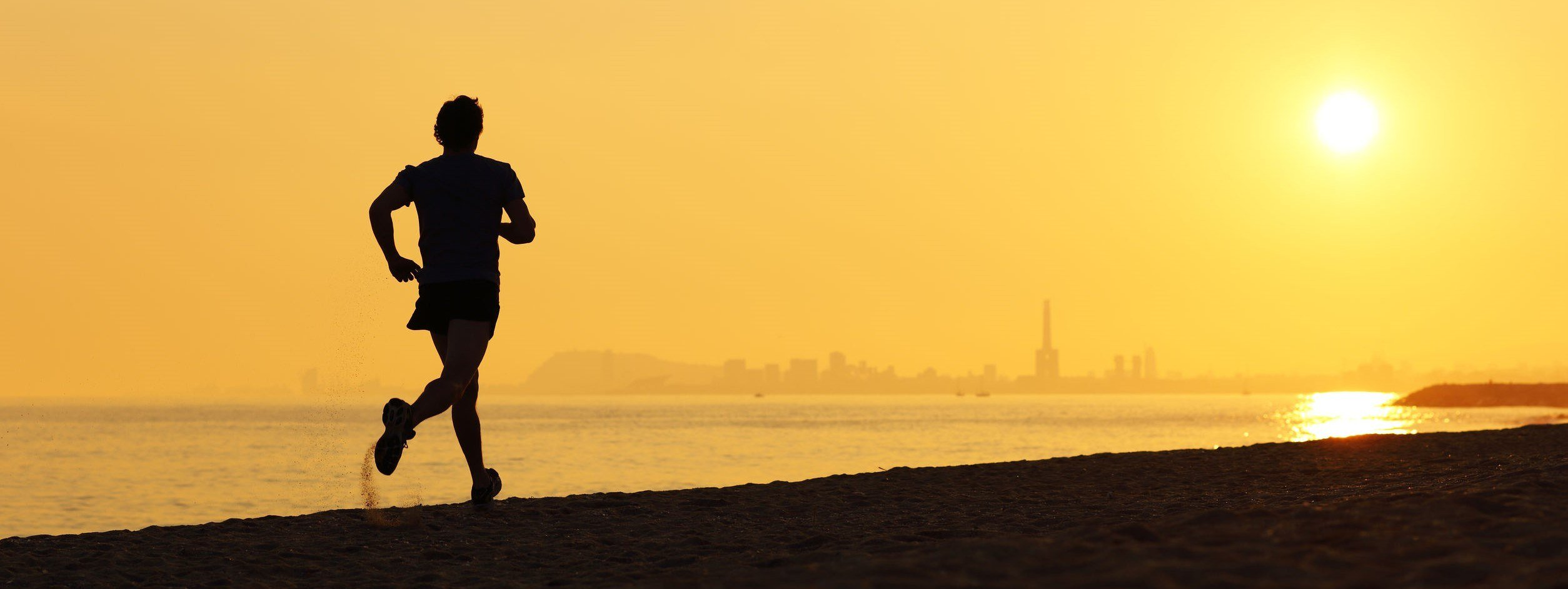 Jogger silhouette running on the beach at sunset with the horizon in the background