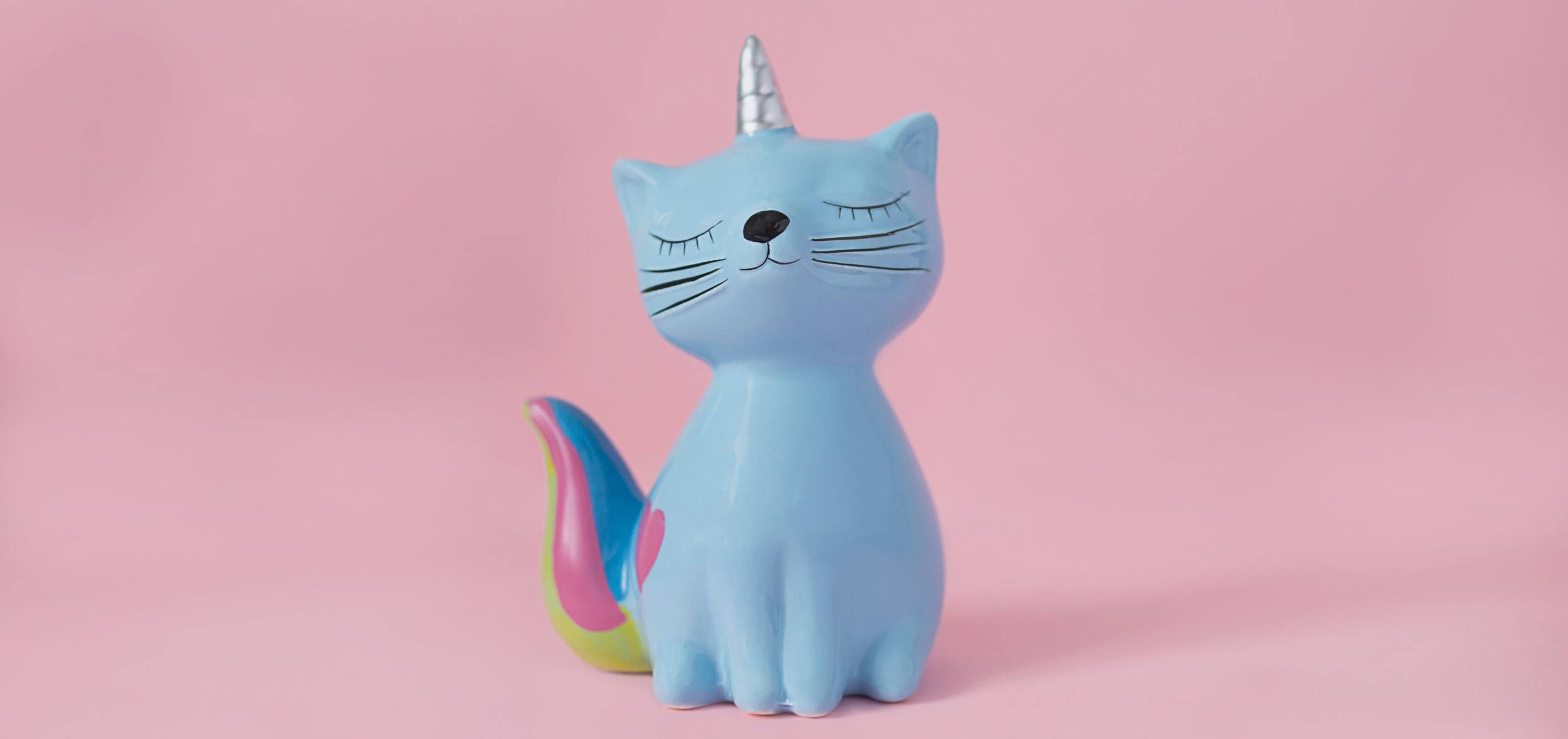 Picture of a ceramic souvenir toy moneybox kitten Korn blue with colorful rainbow tail with closed eyes and unicorn horn on pink background in natural light