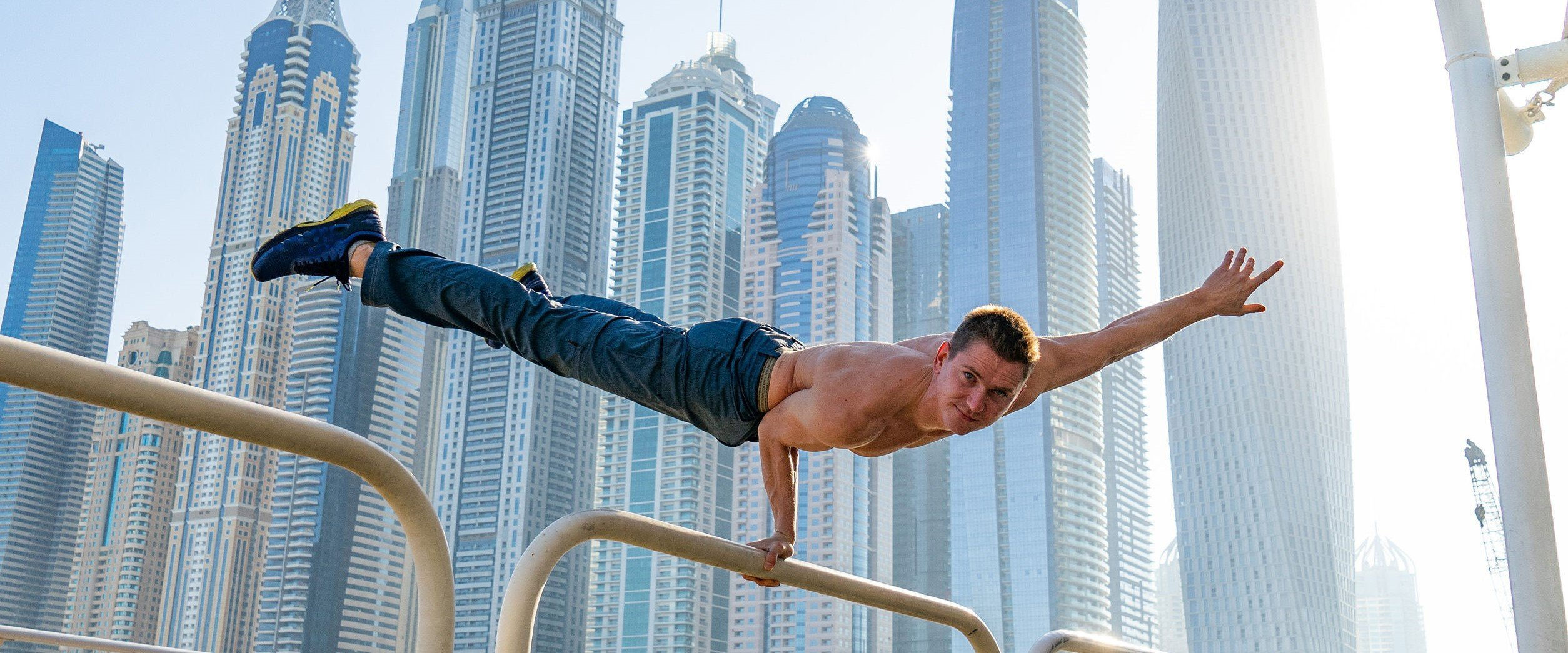 Muscular man doing workout on the street with cityscape of skyscrapers on background in Dubai. Concept of healthy lifestyle and modern