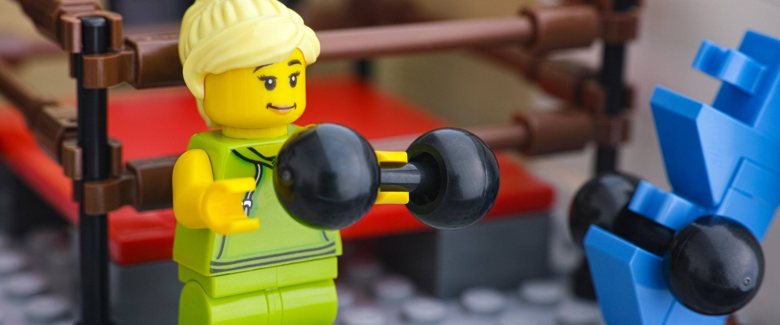 Lego woman minifigure lifting weights in a gym