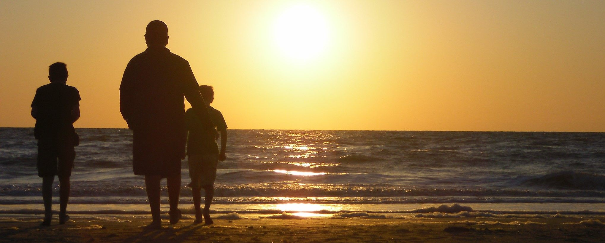 This picture shows a family on the beach looking into the sunset.