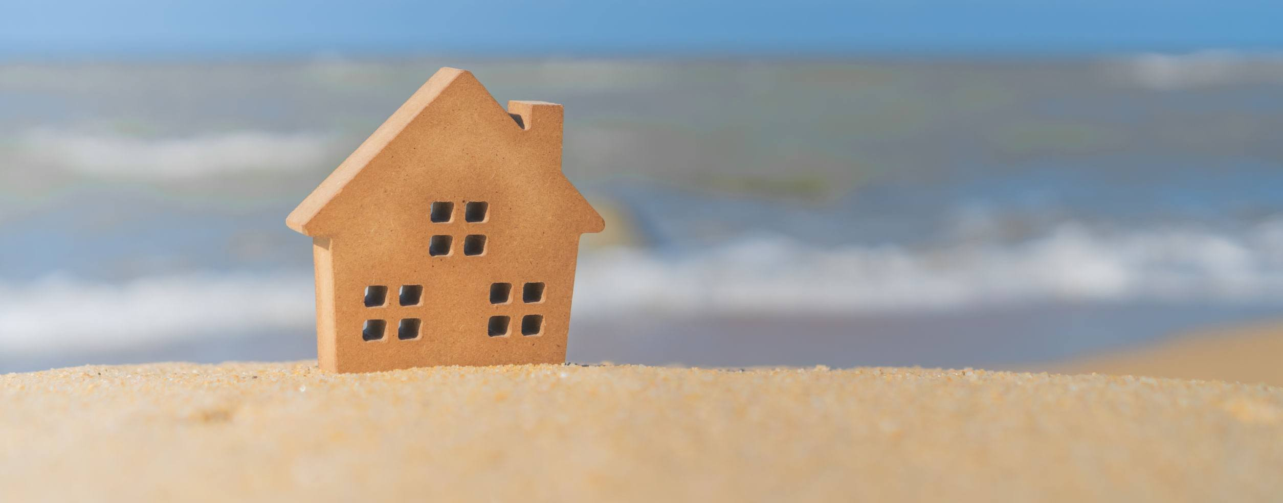 Closed up tiny home models on sand with sunlight and beach.