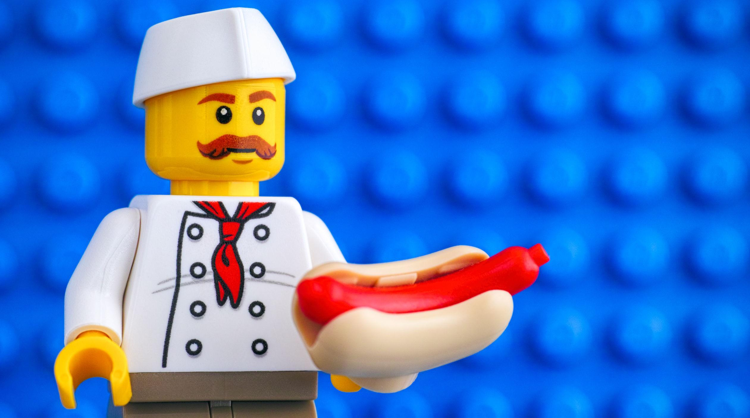 Lego chef with hot dog against blue baseplate backgrounds.