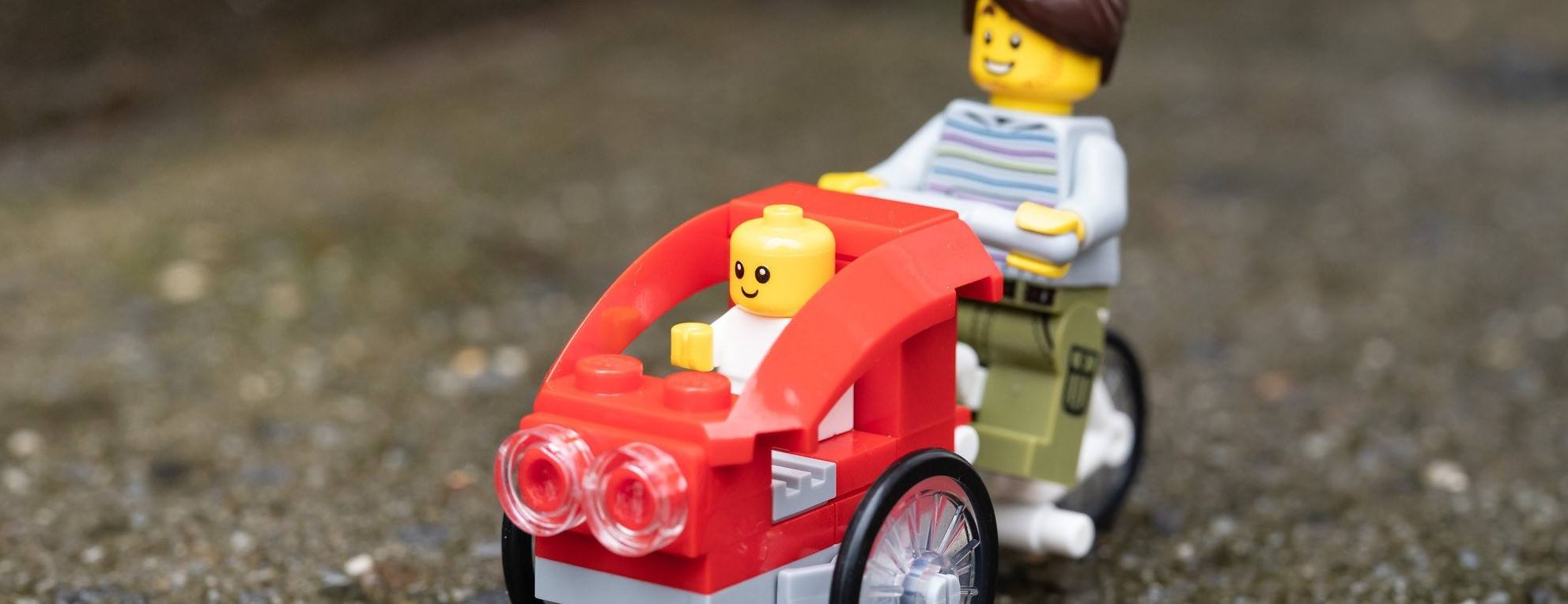 This picture shows a LEGO on a bike with a stroller attached.