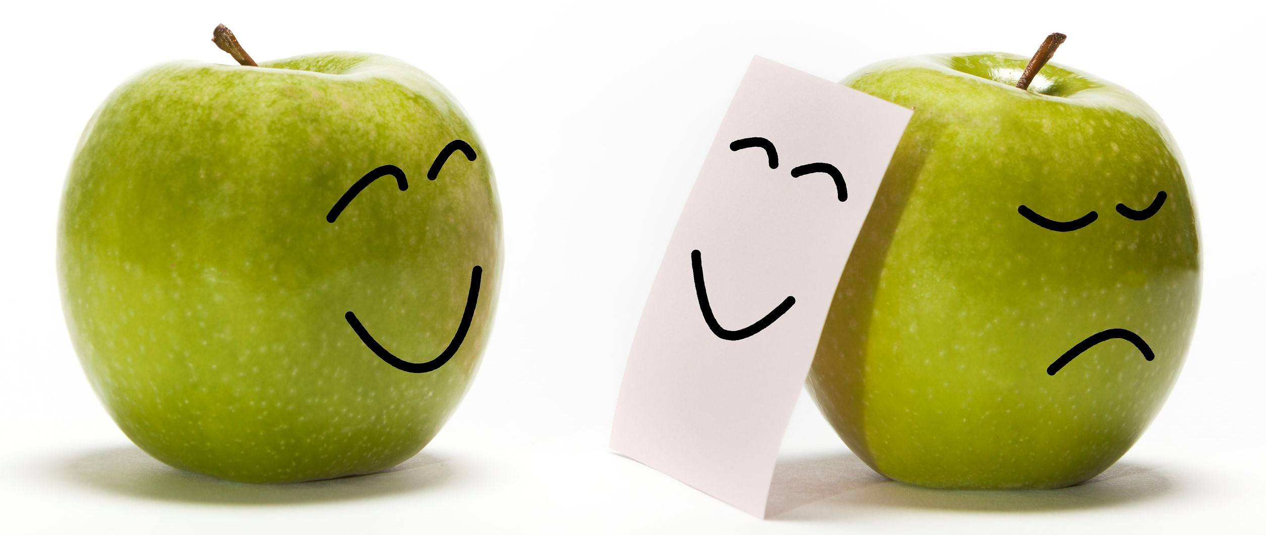n apple smiling to other one that is concealing its sadness behind a smily mask
