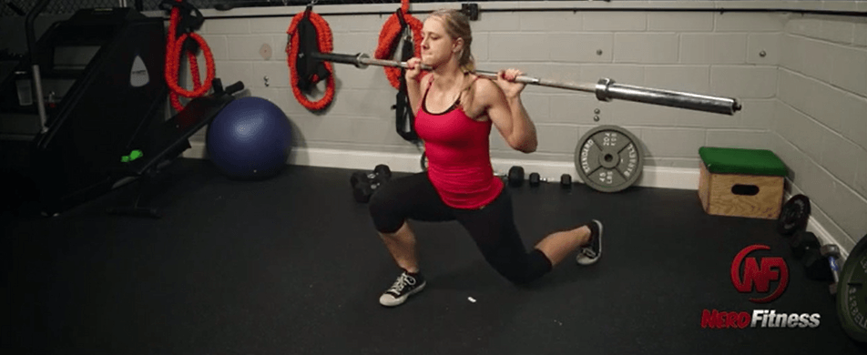 Coach Staci doing a barbell lunge, an advanced lunge variation.