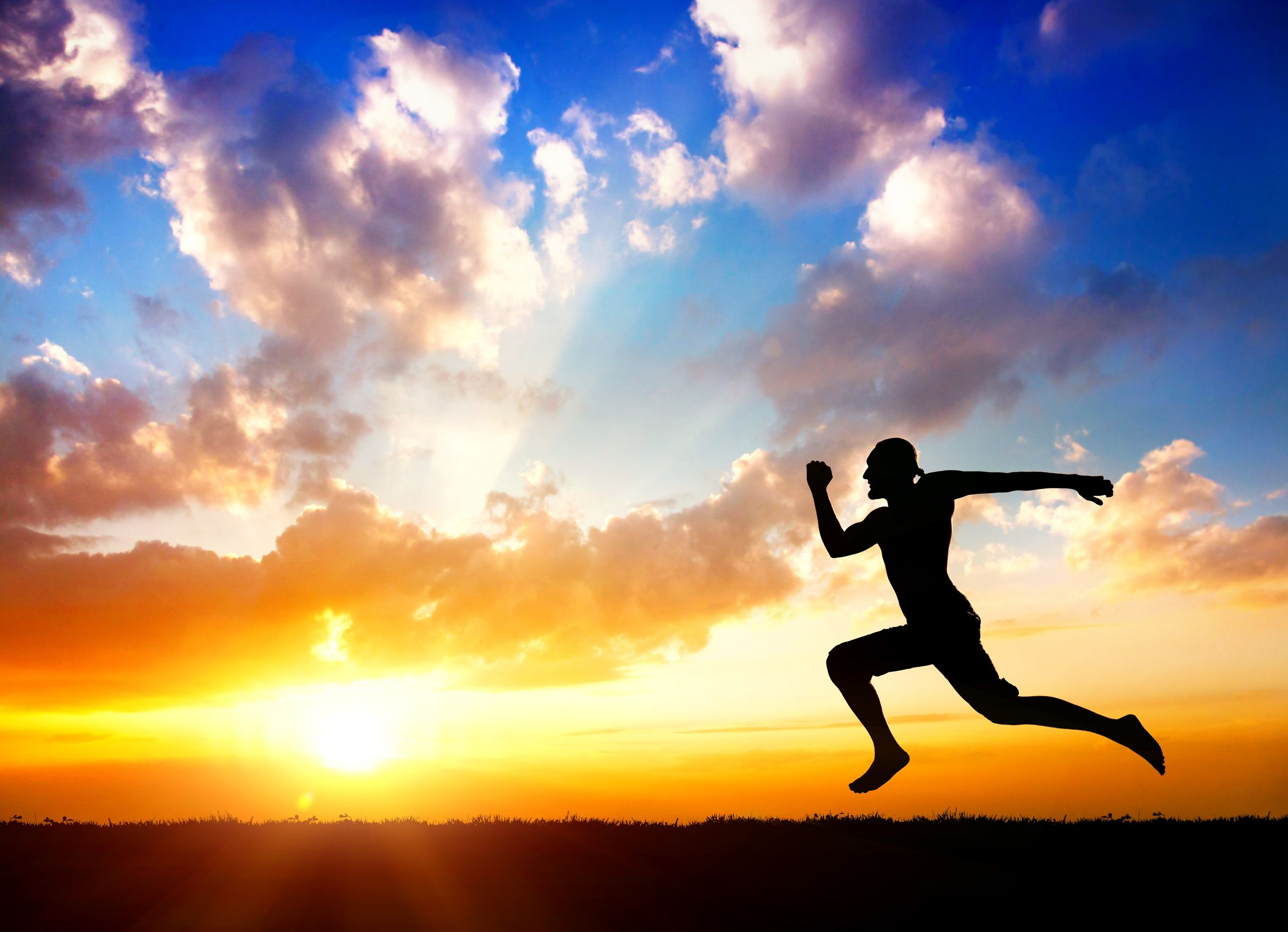 silhouette of man running towards the sun at cloudy background