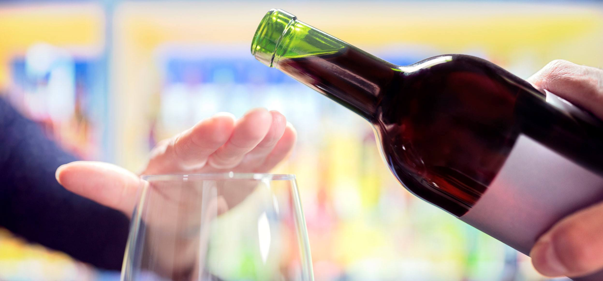 A person putting their hand over a glass, stopping a pour.