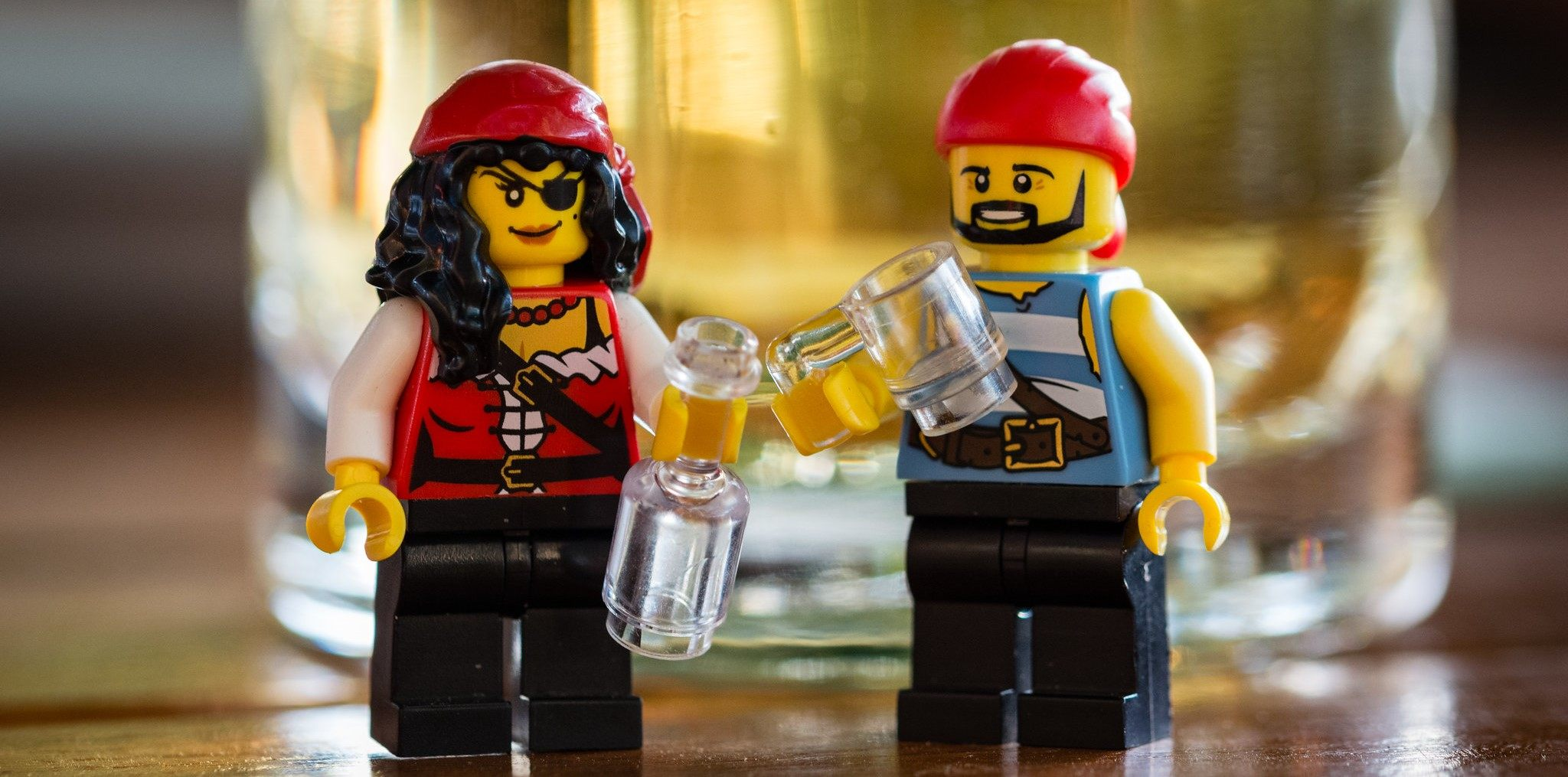 Two pirate LEGOS drinking in front of a glass.