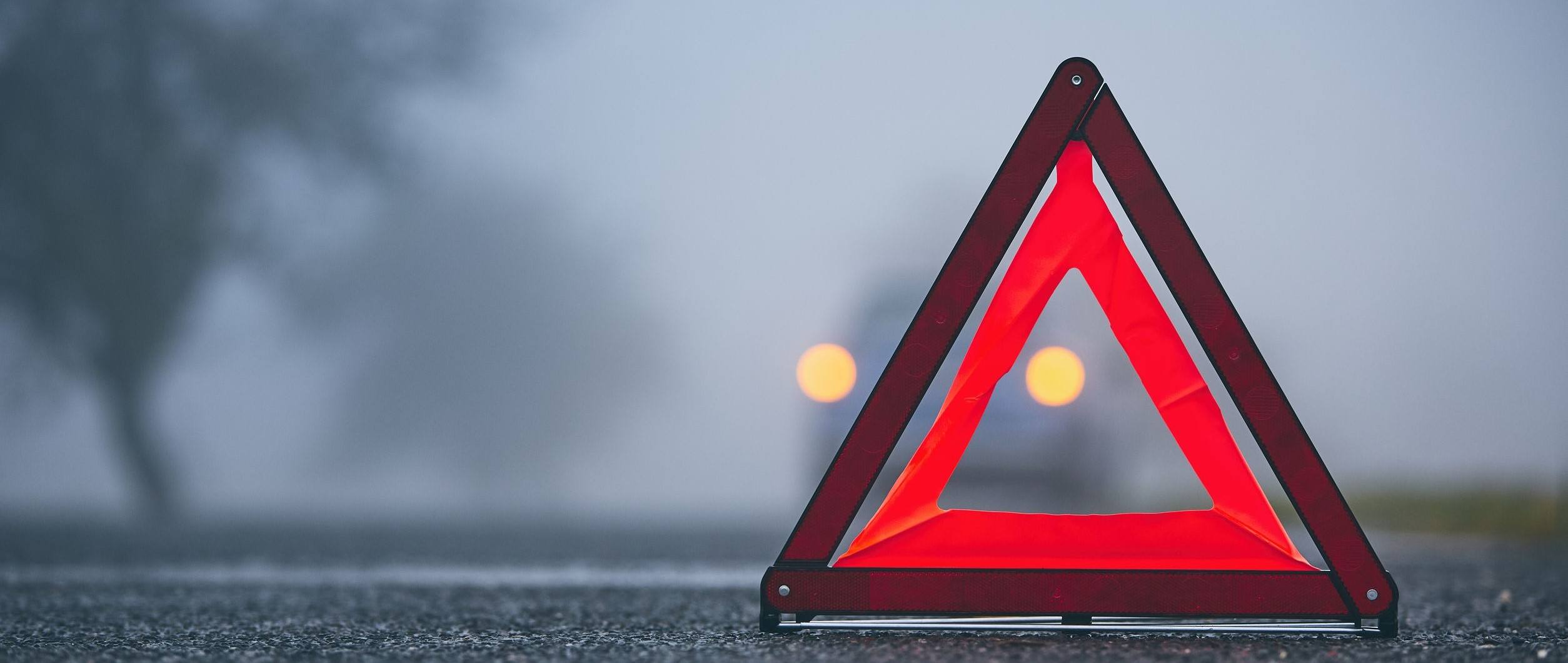 A Warning Triangle on a road with a car in the background.