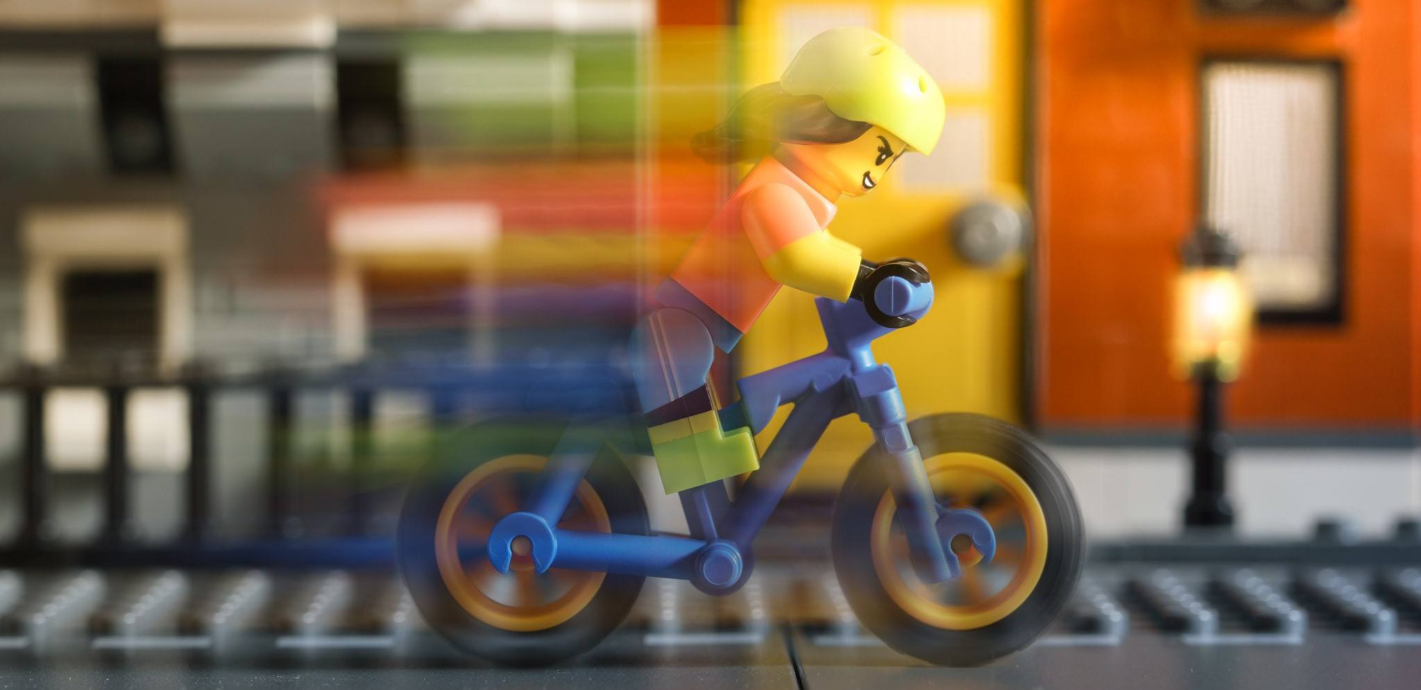 A LEGO going very fast on their mountain bike.