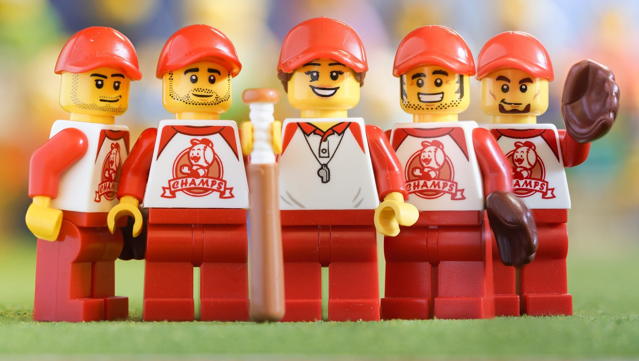This photo shows five LEGO baseballs players smiling.